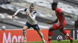 Penyerang Tottenham Hotspur, Gareth Bale, berusaha melewati pemain Southampton, Mohammed Salisu, pada laga Liga Inggris di London, Rabu (21/4/2021). Tottenham menang dengan skor 2-1. (Justin Setterfield/Pool via AP)