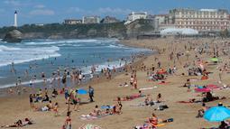 Orang-orang berjemur di pantai Biarritz, Prancis, Kamis (19/4). Masyarakat Paris banyak mengisi musim semi dengan berjemur di pantai. (AP Photo/Bob Edme)