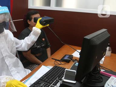 Petugas menggunakan Alat Pelindung Diri (APD) saat merekam mata warga yang mengajukan pembuatan KTP Elektronik di Pondok Aren, Tangerang Selatan, Senin (15/6/2020). Penggunaan APD ini bertujuan meminimalisir kontak fisik sebagai upaya pencegahan penularan Corona COVID-19. (Liputan6.com/Angga Yuniar)