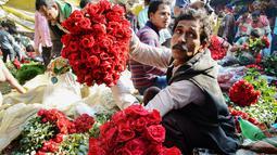 Aktivitas pedangang bunga mawar di pasar bunga grosir di Kolkata, India (7/2). Jelang perayaan hari Valentine, bunga mawar banyak diburu dari tanggal 7 Februari dengan ditandai dengan Rose Day. (AFP Photo/Dibyangshu Sarkar)