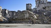 Seorang pria berjalan melewati bangunan yang  hancur di Salaheddine, Aleppo, Suriah, 20 Januari 2018. Gejolak krisis ekonomi menyebabkan lonjakan harga makanan dan kebutuhan dasar di Suriah. (12/6/2020). (AP Photo/Hassan Ammar, File)