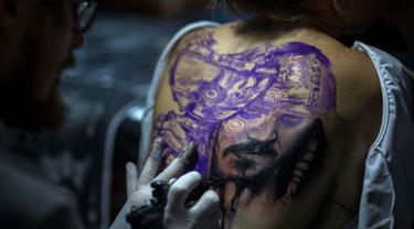 Seorang seniman membuat tato karakter film Pirates of the Caribbean, Jack Sparrow di punggung seorang wanita saat Tattoo Week tahunan di Rio de Janeiro, Brasil (12/1). (AFP Photo/Mauro Pimentel)