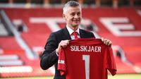 Ole Gunnar Solskjaer menunjukkan jersey Manchester United saat konferensi pers di Stadion Old Trafford, Inggris, (28/3). MU mengontrak Solskjaer selama tiga tahun. (AFP Photo/Oli Scarff)