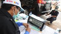 Petugas mengukur kadar emisi kendaraan saat dilakukan uji emisi di Taman Kota 1 BSD, Tangerang Selatan, Rabu (3/10). Dinas Lingkungan Hidup (DLH) Kota Tangerang Selatan menggelar uji emisi guna menekan angka polusi kendaraan. (Merdeka.com/Arie Basuki)