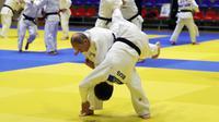 Presiden Rusia, Vladimir Putin mengambil bagian dalam sesi latihan judo bersama atlet nasional Rusia di Sochi, Kamis (14/2). Judo merupakan salah satu olahraga kegemaran Putin yang telah digeluti sejak masa muda. (Mikhail KLIMENTYEV/SPUTNIK/AFP)