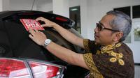 Kepala Dinas Pekerjaan Umum Bina Marga dan Cipta Karya Jateng, AR Hanung Triyono saat menempelkan stiker bertuliskan 'Nek Aku Korupsi Ora Slamet' di mobil dinasnya, Selasa (10/12/2019)