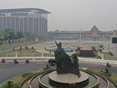 Gambar udara menunjukkan Tugu Zapin ketika kabut asap pekat menyelimuti Pekanbaru, Riau, Minggu (15/9/2019). Menurut BMKG, kualitas udara di wilayah Pekanbaru masih terpantau tidak sehat pada Minggu pagi. (ADEK BERRY/AFP)