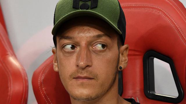 Ekspresi Mesut Ozil saat berada di bangku cadangan saat melihat rekannya bertanding melawan Atletico Madrid di International Champions Cup di Singapura (26/7). Arsenal kalah 3-1 setelah bermain 1-1 di waktu normal. (AFP Photo/Roslan Rahman)