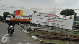 Pengendara motor melintasi spanduk sosialisasi penutupan perlintasan kereta sebidang di Stasiun Pasar Senen, Jakarta, (16/9). Uji coba penutupan perlintasan itu akan berlangsung selama satu bulan pada 1-31 Oktober 2016. (Liputan6.com/Gempur M Surya)