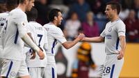 Pemain Chelsea, Pedro dan Cesar Azpilicueta merayakan gol pertama timnya ke gawang Burnledalam lanjutan Premier League di Turf Moor, Jumat (20/4). Gol bunuh diri Kevin Long dan tembakan Victor Moses memenangkan Chelsea dengan skor 2-1. (OLI SCARFF/AFP)