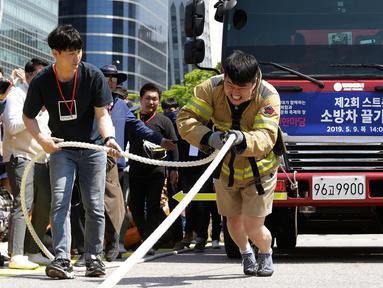 Petugas pemadam kebakaran Lim Sung-joo menarik sebuah truk pemadam kebakaran dengan seutas tali saat Safe Seoul Festival di Seoul, Korea Selatan, Kamis (9/5/2019). Safe Seoul Festival digelar untuk mengampanyekan kesadaran keselamatan. (AP Photo/Ahn Young-joon)