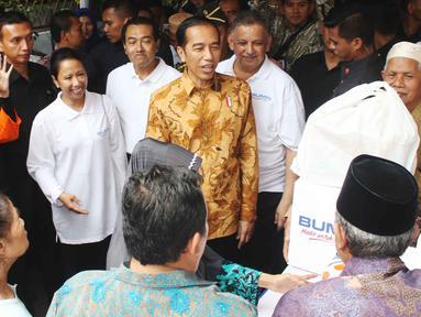 Presiden Joko Widodo (Jokowi) didampingi Menteri BUMN Rini Soemarno dan Dirut Bank BRI Suprajarto menyaksikan pembagian 200 paket Ramadan yang berisi sembako kepada warga di wilayah Penjaringan, Jakarta Utara, Selasa (13/6). (Liputan6.com/Angga Yuniar)