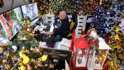 Thomas Jeromin duduk di depan layar komputer di antara pohon-pohon Natal yang dihias di rumahnya di Rinteln, Jerman, Minggu (8/12/2019). Thomas Jeromin memenuhi rumahnya dengan 350 pohon Natal di hampir tiap sudut rumah, mulai dari ruang tamu, dapur sampai kamar mandi. (Ina FASSBENDER/AFP)