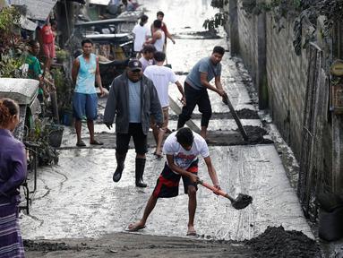 Warga membersihkan jalanan dari abu vulkanik setelah erupsi Gunung Taal di Tagaytay, Provinsi Cavite, Filipina, Senin (13/1/2020). Gunung yang terakhir meletus pada tahun 1977 tersebut melontarkan abu vulkanik mencapai 50.000 kaki (15.000 meter) ke atmosfer. (AP Photo/Bullit Marquez)