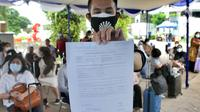 Calon penumpang menunjukkan hasil rapid test antigen di Terminal 2 Bandara Soekarno-Hatta, Tangerang, Banten, Selasa (22/12/2020). Layanan rapid test antigen dibanderol dengan harga Rp 200 ribu. (merdeka.com/Arie Basuki)