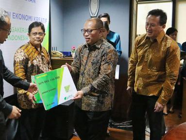 Dirut BPJS Ketenagakerjaan Agus Susanto memberikan kartu peserta usai menandatangani nota kesepahaman, Jakarta, (13/9). Kerjasama dilakukan untuk melindungi para pekerja dan pelaku usaha ekonomi kreatif yang ada di Indonesia. (Liputan6.com/Angga Yuniar)