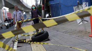 Pejalan kaki melintas di dekat penutup trotoar yang rusak di Jalan RS Fatmawati, Jakarta, Selasa (14/7/2019). Dua buah penutup trotoar di Jalan RS Fatmawati rusak parah, kondisi ini mengganggu kenyamanan dan membahayakan pejalan kaki, terutama pada malam hari. (Liputan6.com/Helmi Fithriansyah)