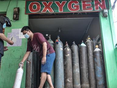 Pekerja melayani pelanggan isi ulang oksigen di agen isi ulang oksigen kawasan Kalimalang, Jakarta, Rabu (27/1/2021). Arif, salah seorang pekerja mengungkapkan permintaan oksigen untuk kebutuhan medis rumahan meningkat 50 persen sejak pandemi Covid-19 mewabah di Jakarta (merdeka.com/Iqbal S Nugroho)