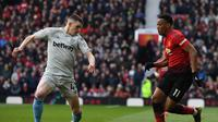 Aksi Anthony Martial melewati bek West Ham, Declan Rice pada laga lanjutan Premier League yang berlangsung di Stadion Old Trafford, Minggu (14/4). Man United menang 2-1 atas West Ham. (AFP/Paul Ellis)