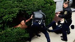 Polisi menahan pengunjuk rasa wanita yang tampil topless di sidang kekerasan seksual komedian Bill Cosby, Pennsylvania, AS, Senin (9/4). Sekitar 50 wanita mengungkapkan pelecehan seksual dan perkosaan yang dilakukan Bill Cosby. (AP Photo/Corey Perrine)