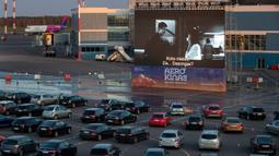 Sejumlah penonton duduk di mobil mereka saat menonton film di bioskop drive-in di area apron bandara , tempat pesawat lepas landas dan mendarat ketika bioskop biasa ditutup karena wabah virus Corona di Vilnius, Lithuania pada 29 April 2020. (AP/Mindaugas Kulbis)
