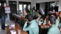 Anggota KPUD Bekasi mengajarkan pemilih pemula penyandang disabilitas mencoblos surat suara saat sosialisasi Pemilu 2019 di SLB Al Gaffar Guchany, Bekasi, Rabu (20/2). (Merdeka.com/Iqbal Nugroho)