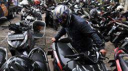 Pegawai kantor Balai Kota DKI Jakarta mengambil motor yang diparkir di halaman Kelurahan Kebon Sirih, Jakarta, Rabu (16/1). Naiknya tarif parkir di IRTI Monas juga menyebabkan halaman Kelurahan tersebut dipenuhi sepeda motor. (Merdeka.com/Iqbal S Nugroho)