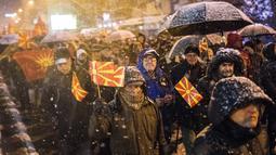 Pengunjuk rasa mengibarkan bendera Macedonia saat menggelar protes di depan gedung Parlemen, Skopje, Selasa (27/2). Di tengah hujan salju, mereka turun ke jalan memprotes wacana pengubahan nama negara mereka. (Robert ATANASOVSKI/AFP)