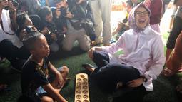 Wali Kota Tangerang Selatan Airin Rachmi Diany mencoba permainan congklak di Taman Bermain Masyarakat (TBM) Kolong Ciputat, Tangsel, Banten, Minggu (22/7). Airin menjajal beragam perminan tradisonal. (Merdeka.com/Arie Basuki)