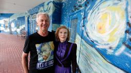 Sepasang suami istri, Nancy Nemhauser dan Lubomir Jastrzebski berpose dekat mural yang menghiasi rumah mereka di Mount Dora, Florida, 18 Juli 2018. Dekorasi The Starry Night pada rumah itu dinilai melanggar aturan kota tempat tinggalnya. (AP/John Raoux)