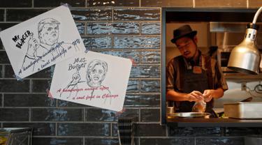 Koki J.S. Burgers Cafe, Yasuhito Fukui menyiapkan Mr. and Mrs. Burger bertema Capres AS Hillary Clinton dan Donald Trump di hamburger joint, Jepang (7/10). Memeriahkan pilpres AS, kafe di Tokyo ini membuat menu yang unik. (REUTERS/Megumi Lim)
