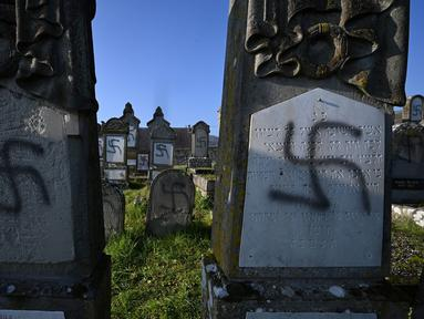 Lambang swastika Nazi pada nisan di pemakaman Yahudi, Westhoffen, dekat Strasbourg, Prancis, Rabu (4/12/2019). Sedikitnya 107 makam menjadi sasaran vandalisme dengan dicoreti lambang swastika Nazi. (AFP/Patrick Hertzog)