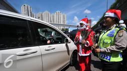Petugas Kepolisian bersama sinterklas saat membagikan bunga dan masker di jalan kawasan Tomang, Jakarta, Rabu (23/12). Menyambut Hari Natal 2015, anggota Kepolisian Polres Jakarta Barat kenakan topi Sinterklas. (Liputan6.com/Yoppy Renato)
