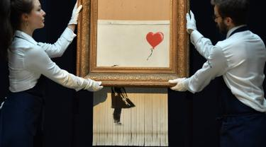 """Karyawan berpose dengan lukisan """"Girl with Balloon"""" di rumah lelang Sotheby London, 12 Oktober 2018. Lukisan karya seniman Bansky itu rusak menjadi potongan-potongan saat terjual seharga sekitar Rp 20 miliar pada lelang 5 Oktober 2018. (BEN STANSALL/AFP)"""