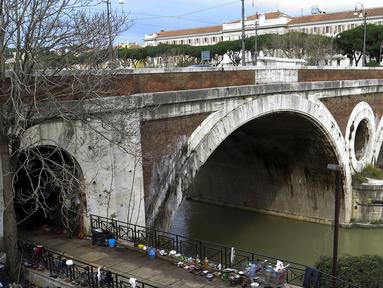 Sejumlah barang milik tunawisma terlihat di kawasan permukiman kumuh bawah jembatan di Sungai Tiber, Roma, Italia (13/4). Para tunawisma menggunakan kayu, karton, hingga terpal plastik untuk membuat tenda sebagai tempat tinggalnya. (REUTERS / Max Rossi)