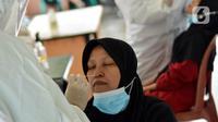 Petugas medis mengambil sampel lendir saat tes swab PCR massal di Kantor Kecamatan Pancoran Mas, Depok, Selasa (5/1/2021). Puskesmas Pancoran Mas melakukan tes Swab PCR kepada warga yang pernah memiliki riwayat kontak erat dengan pasien terkonfirmasi positif Covid-19. (merdeka.com/Arie Basuki)