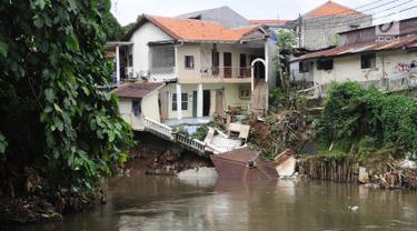 Kondisi bangunan rumah yang amblas akibat longsor di bantaran Kali Ciliwung, Kelurahan Bidara Cina, Jakarta Timur, Senin (19/3). Tak ada korban jiwa atau luka dalam musibah yang terjadi pada Minggu dini hari tersebut. (Liputan6.com/Herman Zakharia)