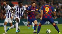 Megabintang Barcelona, Lionel Messi, mengontrol bola melewati hadangan pemain Real Valladolid, Mohammed Salisu dalam pertandingan pekan ke-11 La Liga  di Camp Nou, Selasa (29/10/2019). Barcelonamenutup laga dengan kemenangan 5-1 lewat gol tambahan dari Lionel Messi dan Luis Suarez. (AP/Joan Monfort)