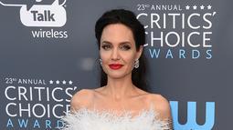 Angelina Jolie berpose untuk fotografer setibanya pada acara Critics Choice Awards 2018 di Santa Monica, California, Kamis (11/1). Jolie yang selalu muncul dengan outfit tertutup, kali ini ia berdandan lebih seksi dan glamor. (Jordan Strauss/Invision/AP)