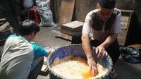 Ayep (63), perajin tempe tengah mengolah kedelai di Komplek Kopti RT 02 RW 10, Kelurahan Margahayu Utara, Kecamatan Babakan Ciparay, Kamis (31/12/2020). (Liputan6.com/Huyogo Simbolon)