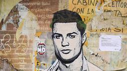 Sebuah mural dengan gambar bintang Juventus, Cristiano Ronaldo, yang terdapat di Milan, Senin (19/3). Mural berjudul Cristiano's Secret ini karya seniman Italia, TvBoy. (AFP/Miguel Medina)