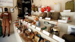 Baju tempur, bendera, senjata, hingga pakaian untuk bom bunuh diri yang pernah digunakan ISIS di sebuah museum di Erbil, Irak, 12 Mei 2019. Museum itu memamerkan memorabilia perang dan benda-benda yang berhasil direbut dalam pertempuran dengan ISIS. (REUTERS/Azad Lashkari)