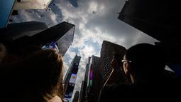 Sejumlah orang mengabadikan fenomena gerhana matahari parsial di langit New York, Senin (21/8). Gerhana matahari akan terjadi selama 100 menit dan selama dua menit kondisi langit akan gelap gulita di siang hari. (AP Photo/Michael Noble Jr.)