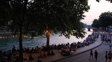 Orang-orang duduk saat berkumpul di tepi sungai Seine sebagai bagian dari acara musim panas Paris Plages di Paris, Prancis (7/7). (AFP Photo/Francois Guillot)
