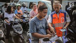 Petugas PT KAI Daop I menggelar sosialisasi tertib berlalu lintas di pintu perlintasan sebidang kawasan Bukit Duri, Jakarta, Selasa (17/9/2019). Sosialisasi dilakukan karena banyaknya kecelakaan akibat ketidakdisiplinan pengendara. (Liputan6.com/Faizal Fanani)
