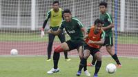 Pemain Timnas Indonesia U-22, Andy Setyo, berebut bola dengan Gian Zola saat latihan di Stadion Madya Senayan, Jakarta, Selasa (22/1). Latihan ini merupakan persiapan jelang Piala AFF U-22. (Bola.com/Yoppy Renato)