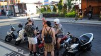 Turis mancanegara berkumpul di depan papan izin mendirikan bangunan (biru) di bekas lokasi bom Bali Sari Club di Kuta, Bali, Jumat (26/4). Pemkab Badung memberikan izin pembangunan restoran lima lantai di lokasi pemboman Bali yang terjadi pada tahun 2002 silam tersebut. (SONNY TUMBELAKA/AFP)