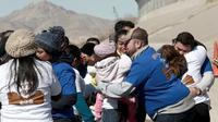 Suasana haru saat warga Meksiko bertemu keluarga dan kerabat mereka di perbatasan Meksiko-AS di Ciudad Juarez, Meksiko (28/1). Dengan waktu yang singkat, akhirnya mereka dapat melepas rindu setelah lama berpisah. (AP Photo/Christian Torres)
