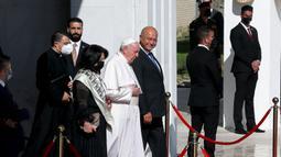 Paus Fransiskus (tengah) berjalan dengan Presiden Irak Barham Salih menuju pesawatnya usai mengakhiri kunjungannya ke Irak di Bandara Baghdad, Irak, Senin(8/3/2021). Paus meninggalkan Irak usai membawa harapan kepada minoritas Kristen yang terpinggirkan di negara itu. (AP Photo/Khalid Mohammed)