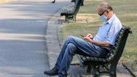 Seorang pria yang memakai masker duduk di bangku taman di Brussel, (12/8/2020). Penggunaan masker menjadi wajib di tempat umum di Brussel karena kasus Covid-19 naik ke tingkat kewaspadaan yang menempatkan kota itu di antara yang paling parah terkena dampak corona di Eropa. (François WALSCHAERTS/AFP)